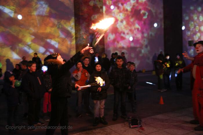 Clown Herr Balzer spielt und jongliert mit Feuerfackeln und spuckt Feuer über die Köpfe des Straußberger Publikums.