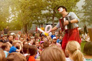Clown Herr Balzer spielt Kindertheater mit Luftballontieren und Akkordeonmusik, hier im Garten des jüdischen Museums Berlin.