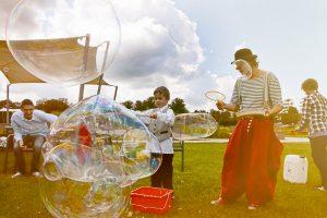 Der Clown Herr Balzer macht im Schloßpark Oranienburg Riesen - Seifenblasen.