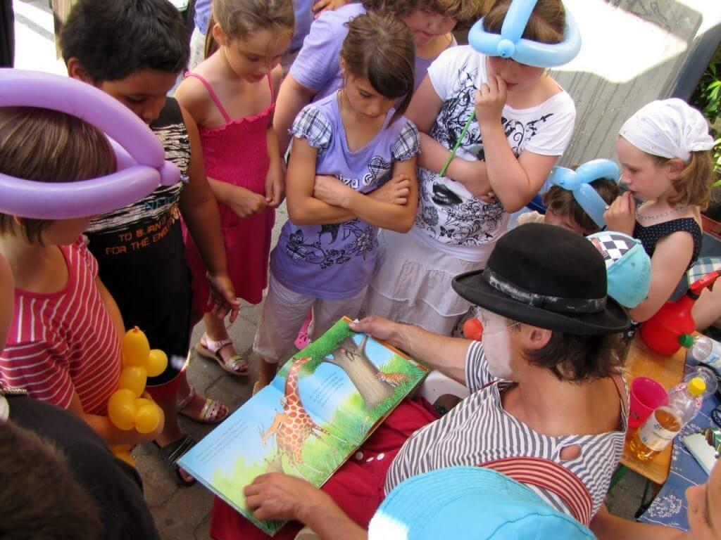 Der berliner Clown Herr Balzer liest über Giraffen zum Sommerfest in Saaken.